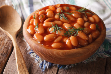 white beans in tomato sauce in a wooden bowl