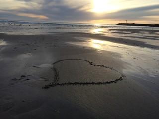 corazon pintado en la arena en el atardecer