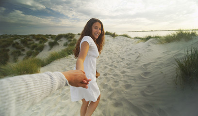 Young woman holding hands with the viewer on a sandy beach