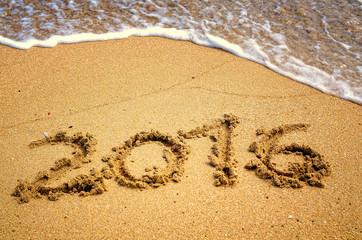 happy 2016 written on the sand