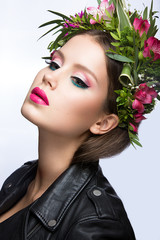 Beautiful girl with a lot of flowers in their hair and bright pink make-up. Spring image. Beauty face