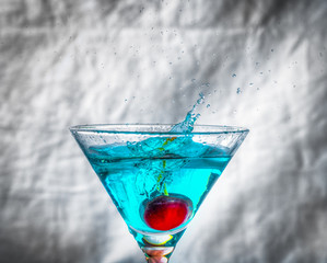 cerise tombant dans un verre de cocktail