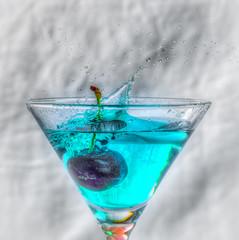 cerise tombant dans une verre de liquide