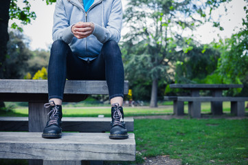 Woman wearing boots sitting on bench