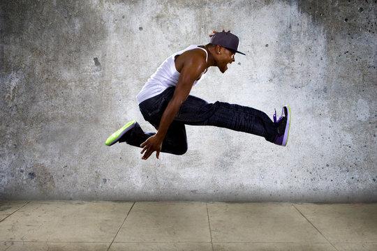 hip hop dancer jumping high on concrete