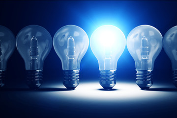 Illuminated Light Bulb standing out from the others Light Bulbs. Individuality Conceptual Background