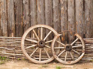 Wheels in the wooden log house in Russian village in the middle