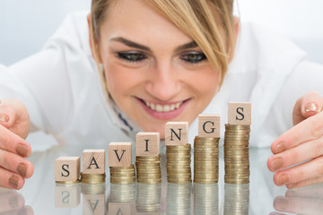 Businesswoman Covering Savings Block On Coins