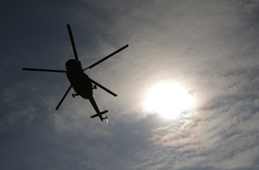 Helicopter silhouette sun above