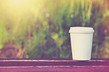 paper cup of coffee on natural morning background