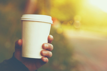 hand holding paper cup of coffee on natural morning background