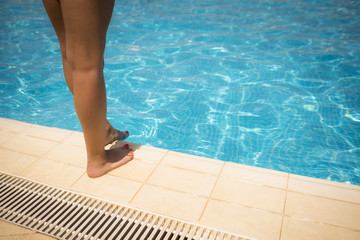 Woman standing on edge of the swimming pool.