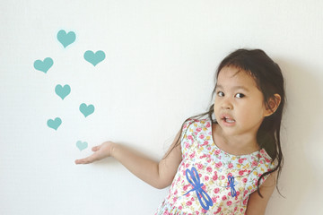 Cute girl showing many draw heart shape blowing in the air