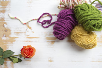 balls of wool on wooden background with orange rose