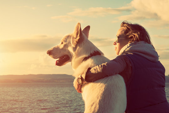 Young attractive girl with her pet dog at a beach, colorised