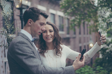 Bride and groom doing selfies in vintage pastel colors