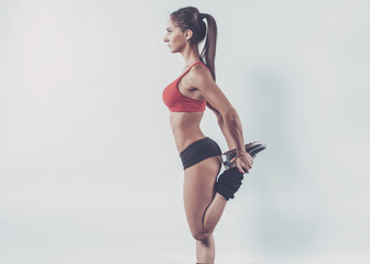 Muscular active athlete woman standing looking forward leg in
