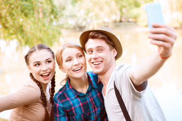 Three young people doing selfie in park