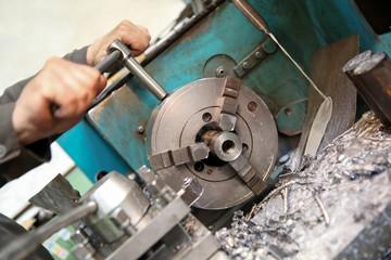 operator fixing workpiece in manual lathe machine chuck