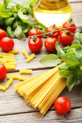 Spaghetti, basil and tomatoes on grey wooden background