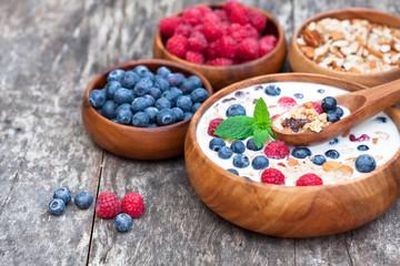 healthy breakfast muesli with berries and milk in wooden plate