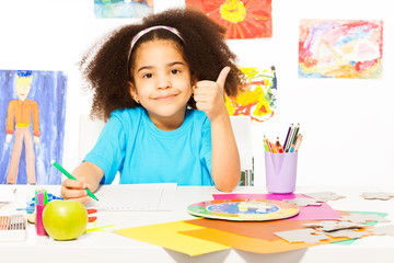 African girl holds thumbs up at the desk writing