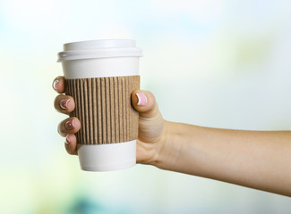 Female hand with paper cup on bright blurred background
