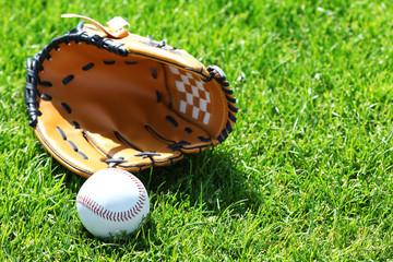 Baseball ball and glove on green field