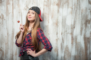 Cheerful Hipster woman with hat and candy