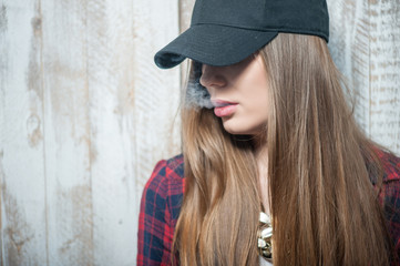 Pretty hipster woman with hat and cigarette