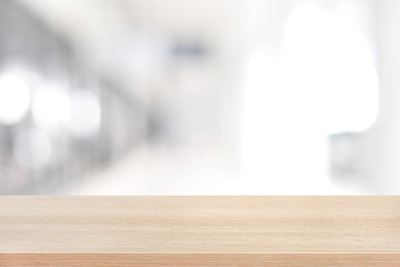 Wood table top on blurred white gray background of building hall