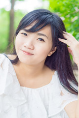 Portrait of young smiling Asian woman in park