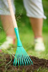 Erde glatt streichen mit dem Laubrechen, Gartenarbeit