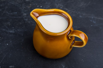 Jug with milk on a black background