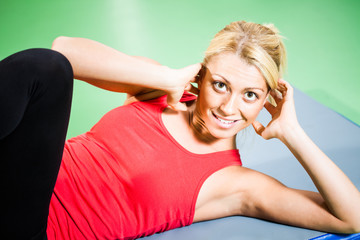 Young woman exercising in gym, doing crunches