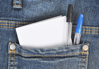 Denim pocket with two pens and a piece of paper