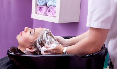 young woman at hairdresser wash hair