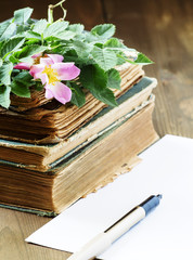 Old books, blank paper, flowers of wild roses in vintage style,