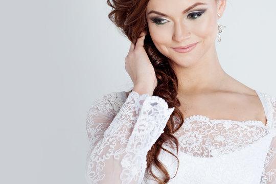 Portrait of happy bride in wedding dress, white background