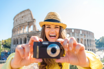 Laughing woman looks up from taking photo with Colosseum behind