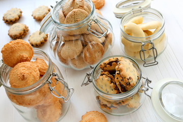 Shortbread biscuits in jars on a white wooden background