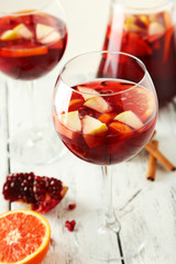 Glasses of sangria on white wooden background