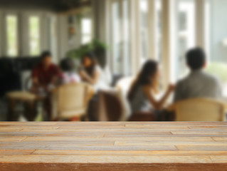 Empty wooden table and blurred people in cafe background