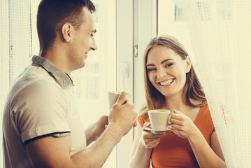 young couple drinking tea or coffee at home