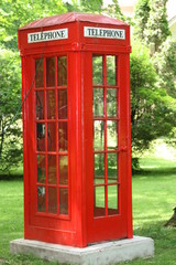 English red telephone booth in park settig