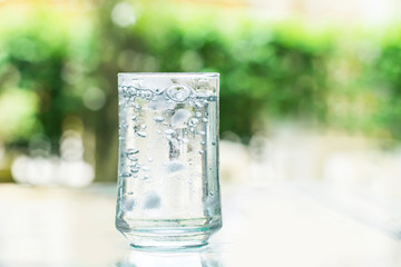 glass of Cool fresh drink with ice cube and bubble on the  table