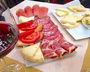 Tagliere di salumi e formaggi toscani con vino rosso.
