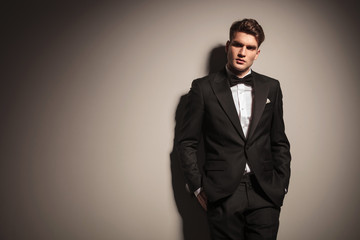 Elegant young business man leaning on a grey wall
