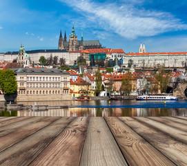 Wooden planks vith view of Prague Charles bridge over Vltava riv