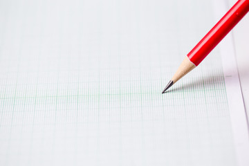 close-up red pencil on graph paper background